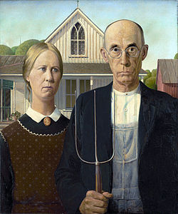 Man and woman with stern expession stand side-by-side. The man hold a pitch fork.